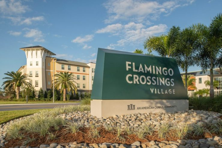 Photo of the main entrance sign to Flamingo Crossings Village in front of one of the apartment buildings