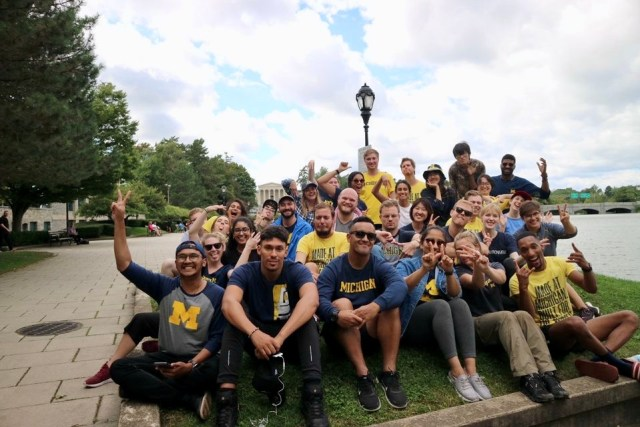 Group of Michigan students wearing Michigan shirts with their hands in peace signs in Washington DC. The weather is partly cloudy and there are trees to the left of them and water to the right.