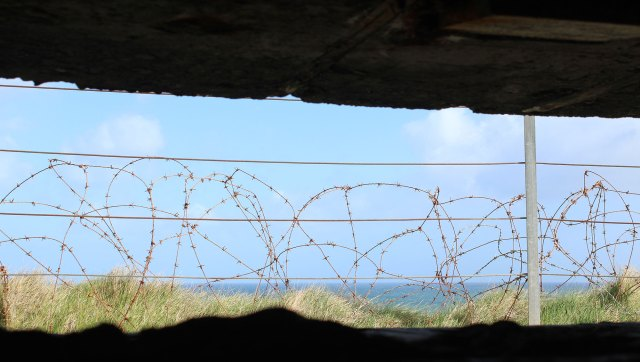 The view of Omaha Beach from behind barbed wire of a bunker