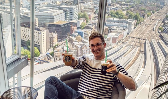 Asher Michelson poses inside The Shard with two Starbucks cups in hand.