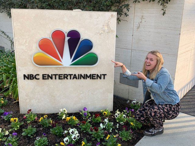 Kathryn Jankowski stands with the NBCUniversal sign in L.A.