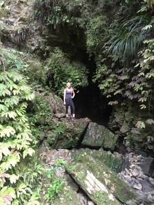 Standing in front of a cave that lead way back behind the greenery