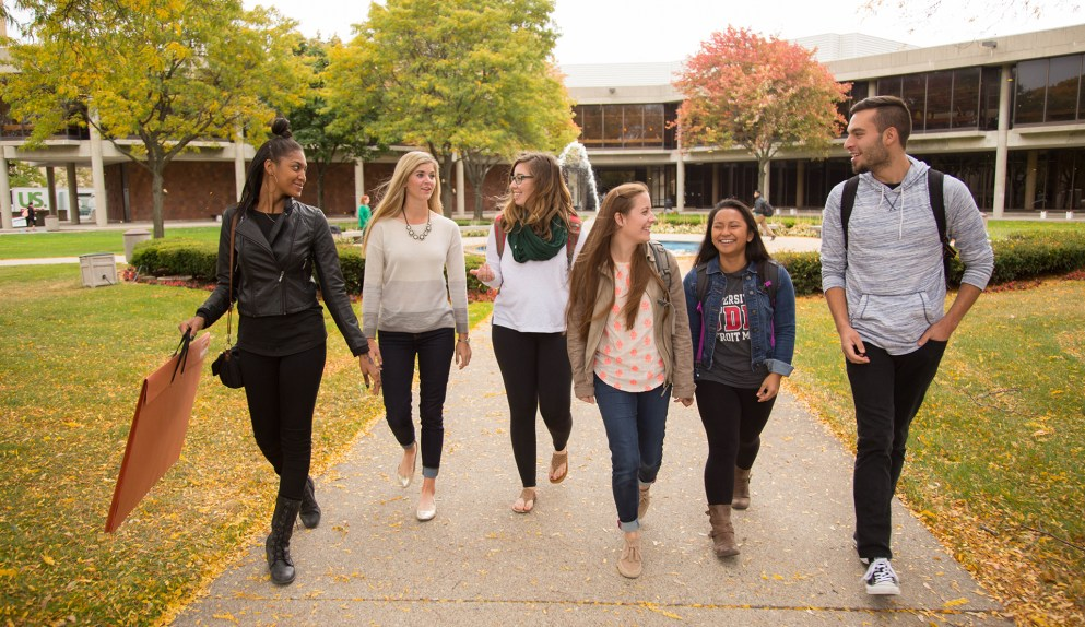 A group of young students in the fall walking across the McNichols Campus.