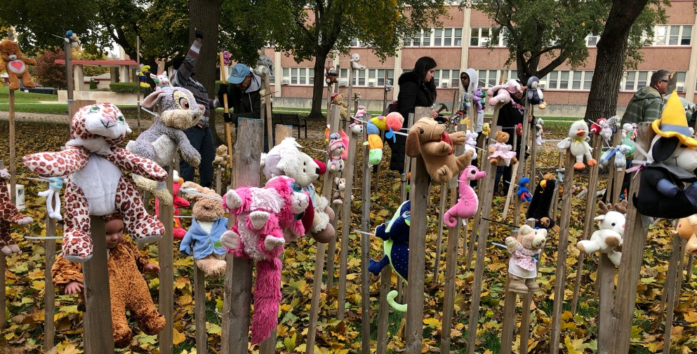 Immigration Art Installation toys attached to wooden stakes