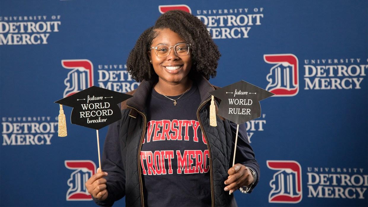 Female Detroit Mercy Class of 2020 graduate celebrating at Grad Salute.
