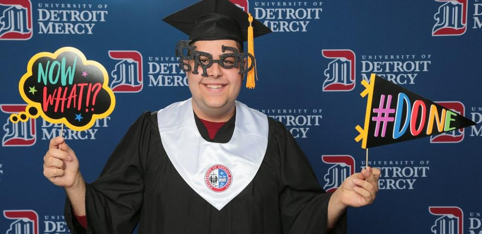 Detroit Mercy Class of 2020 graduate celebrating at Grad Salute.