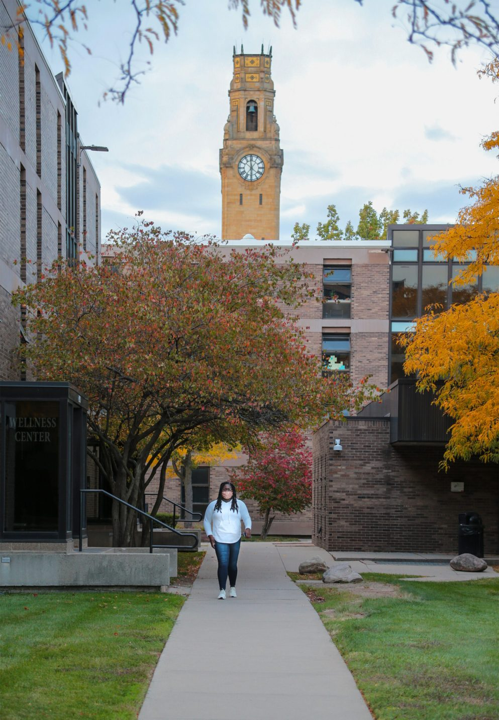 A Detroit Mercy student steps out of the dorms on their way to Fall Festival while wearing a mask.