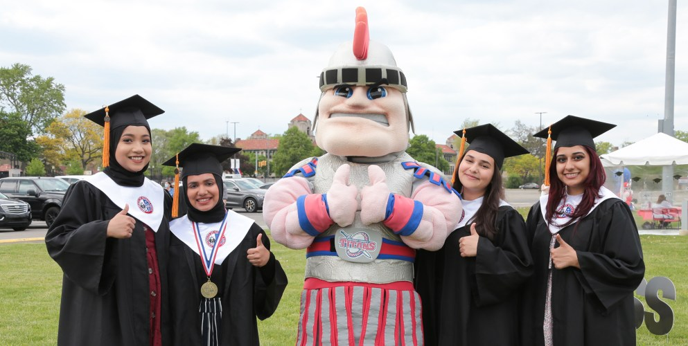 Four class of 2021 graduates poses with Tommy Titan.