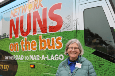 """A photograph of Sr. Simone Campbell, SSS, in front of the Network Nuns on the Bus vehicle. The text on the bus includes """"on the road to Mar-a-Lago"""" and many signatures on the bus are visible."""