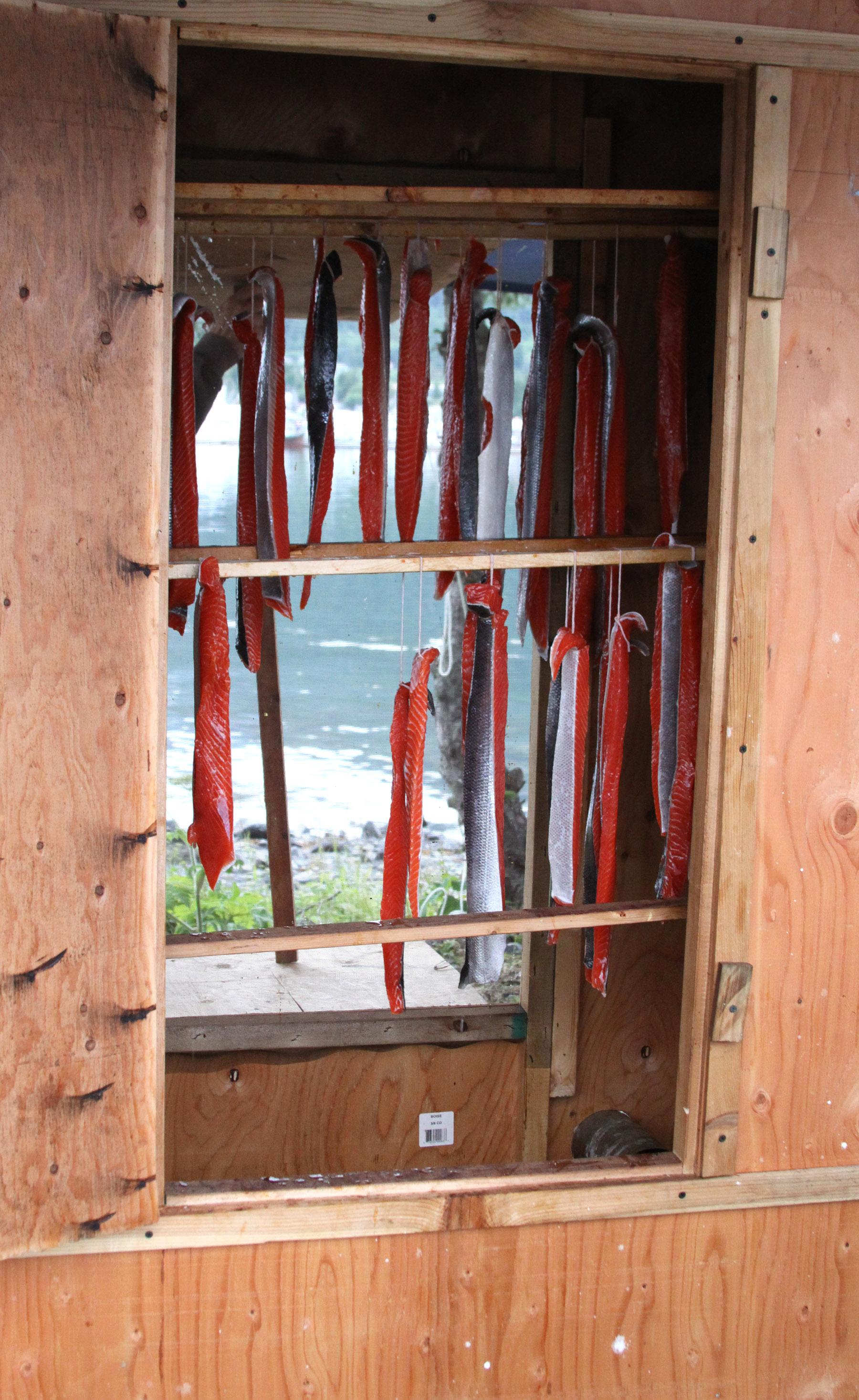 Sockeye salmon hangs from the racks in the smoker.