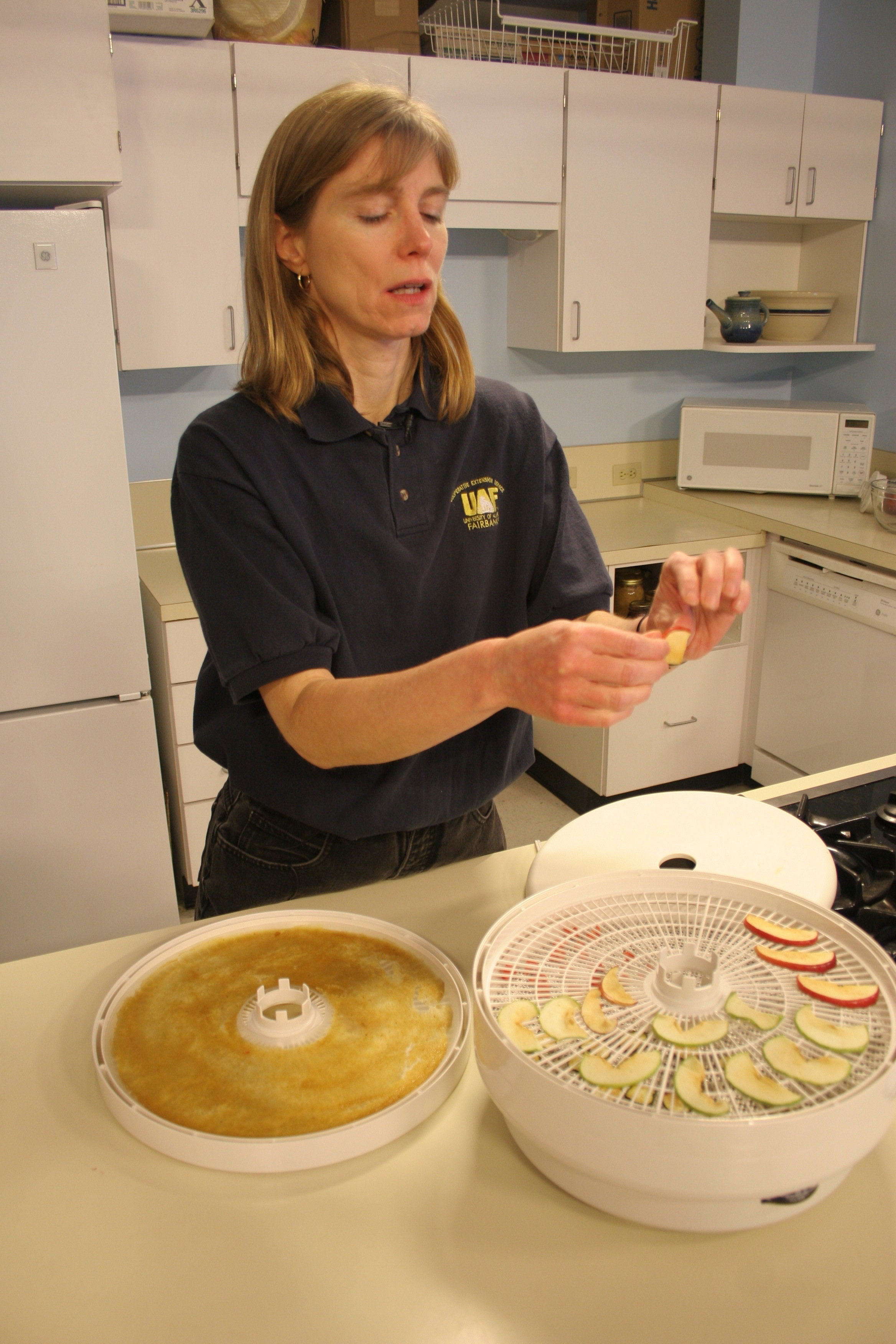 Julie Cascio of UAF Cooperative Extension Service's Health, Home and Family Development program in the Palmer/Mat-Su district demonstrates how to dry apples