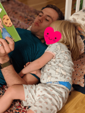 a father reads a book to his toddler-age daughter