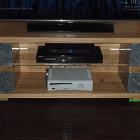 A TV stand with alternating Ash and polished concrete layers, with an edge lit polycarbonate centre shelf.
