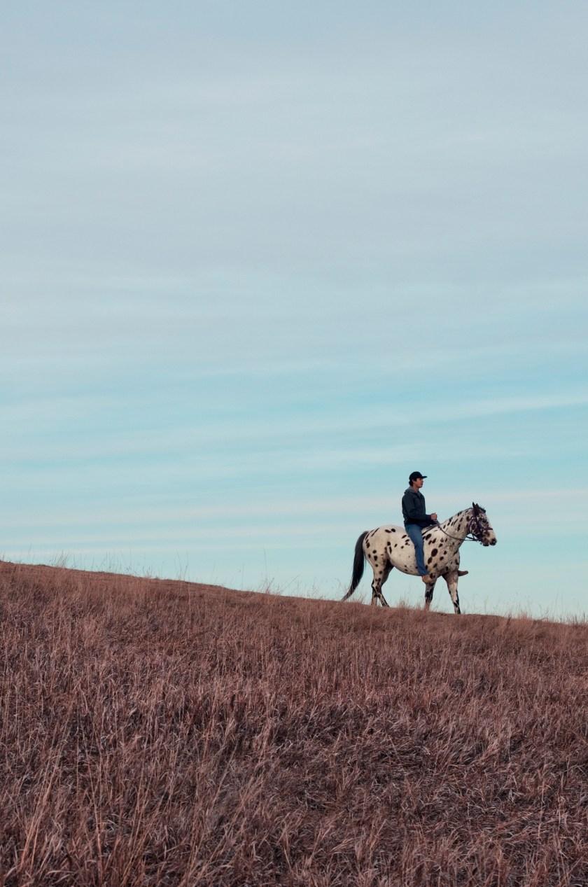 Man riding horse down Media Hill. Photo credit: Natalie Escobedo