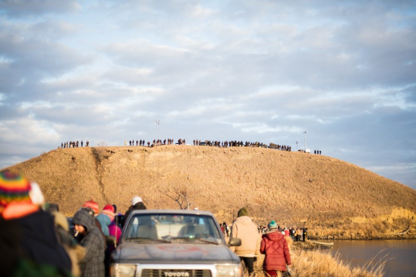 People participating in prayer circle with militarized police occupying Turtle Island in the background, Photo credit: Analu M. Lopez