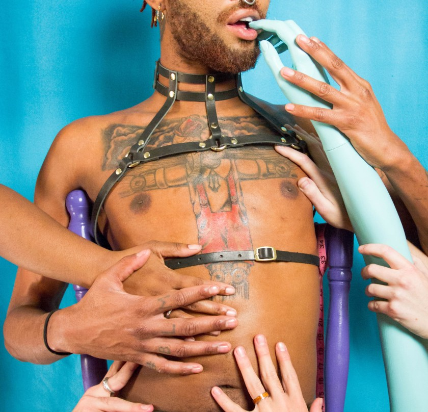 A seated model with a beard and a large chest tattoo wearing one of Alamo's harnesses. Several hands reach for the person's chest. Photo credit: Jamie Jameson.