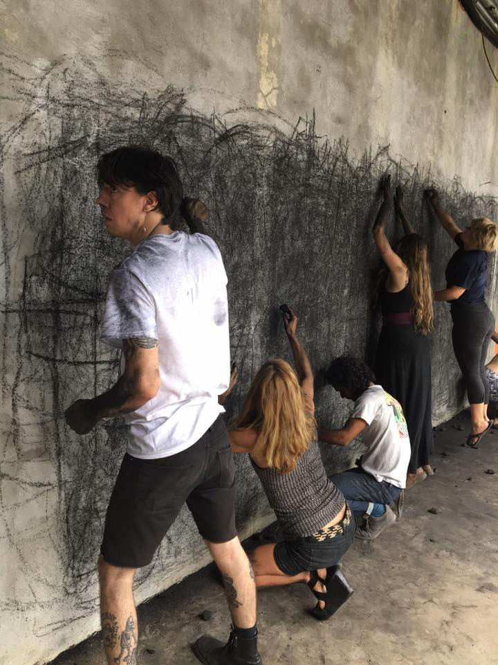 An image of five people in front of a wall, using wide gestures and positions to draw with charcoal in an abstract manner.