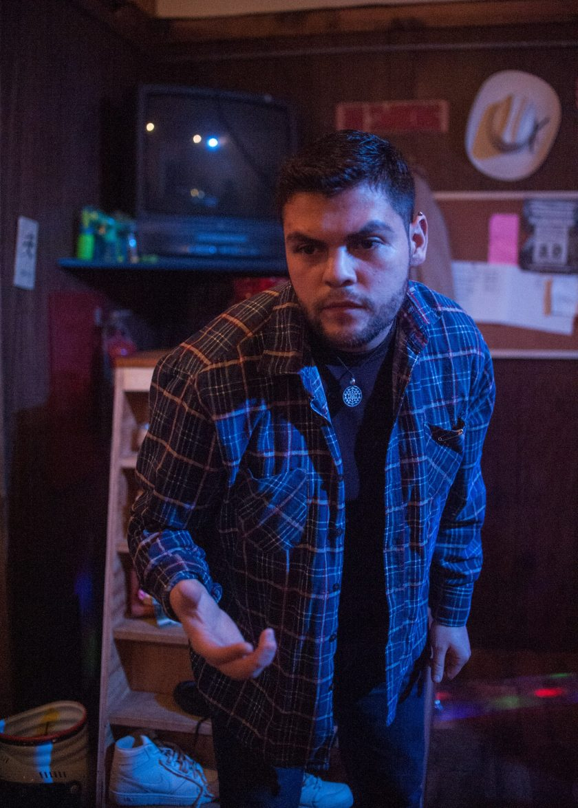 "Anthony Soto leans foward, with his right hand outstretched in a scene from ""Meet Juan(ito) Doe."" Photo by William Camargo."