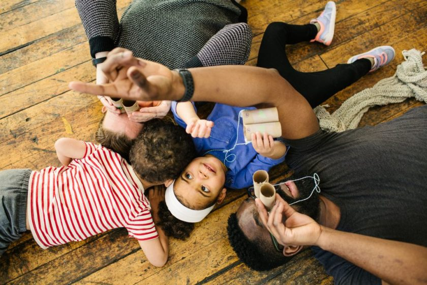 This photograph shows, from above, the artist, his wife Katie, and their twin toddlers lying on a wooden floor, with the adults and daughter holding cardboard tubes resembling binoculars and looking up. The artist's left arm cuts across the image as he points toward the ceiling. His daughter's eyes look where he's pointing. Photo by Becca Heuer Photography.
