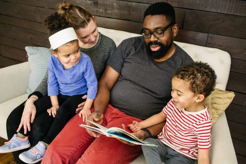 The artist, his wife Katie, and their toddler twins sit together on a large plush chair, in front of a wooden wall. Saleem holds a children's book open in his lap and the others look on. His son points at the book and smiles. Photo by Becca Heuer Photography.