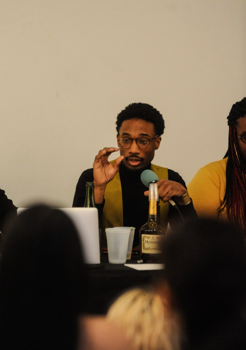 A Hoodoisie co-host and journalist, Charles Alexander Preston, sits at the table and talks into the microphone. Preston wears glasses, a black sweater, and vest. Photo by William Camargo