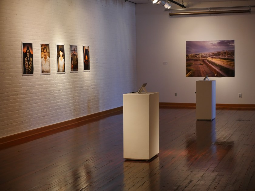 An installation shot of the exhibition shows portraits of El Paso and Juarez locals, a drone shot of landscape around the fence, and two iPads with videos playing. Image courtesy of the artists.