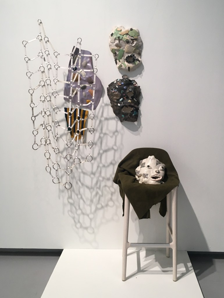 Courtesy of the artist. A stool covered with black cloth is on the right hand side of the image with a ceramic mask. Two marks are hanging on the wall above it. A white piece hands on the left side of the wall.