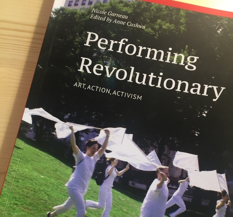 "Image shows the cover of the book ""Performing Revolutionary: Art, Action, Activism."" The cover shows several people wearing white waving white flags while running down a hill. in Grant Park."