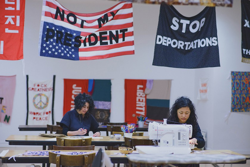 """Protest Banner Lending Library"", 2016–present. Aram Han Sifuentes and a participating at different tables sewing at the Chicago Cultural Center with protest banners hanging above them that read ""NOT MY PRESIDENT"" and ""STOP DEPORTATIONS."" Photo by eedahahm."
