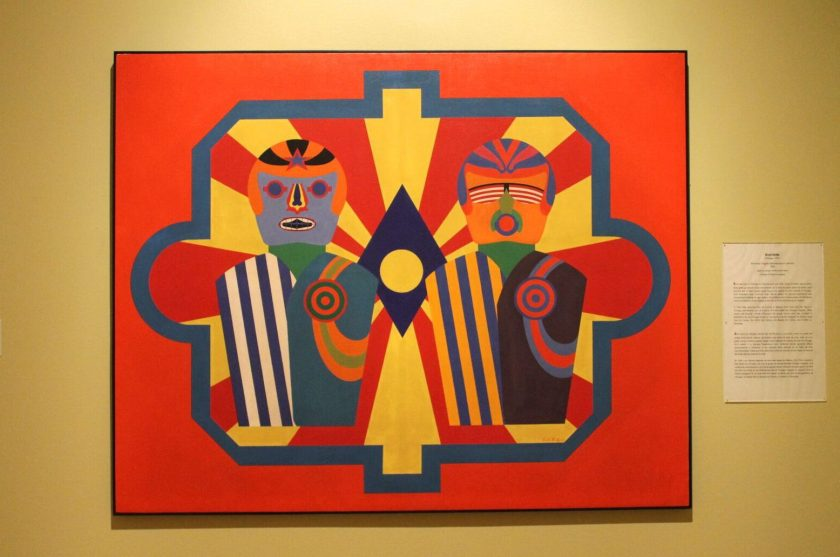 Astronaut Targets by Errol Ortiz. Red and yellow rays emanate from a blue and yellow diamond shape in the background of the painting. Two colorful figures wearing striped suits, and helmets with stylized features stand in the foreground side by side. Photo by Melissa Patiño Cervantes.