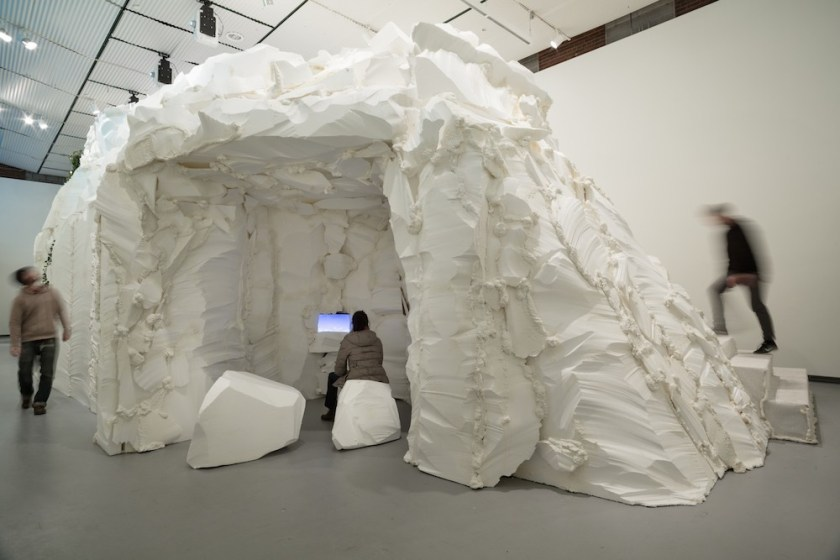 """Installation view of """"who cares for the sky"""" at Hyde Park Art Center, 2016. The image shows a large white mountain structure in the middle of a gallery space. Carved into the side is an opening with white rocks where a person is sitting and looking at an image on a screen. Photo courtesy of her website, sabinaott.com."""