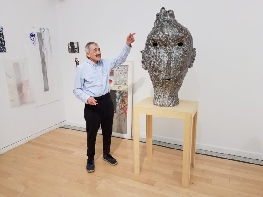 This photo shows one corner of the gallery. David smiles and points up toward the top of a tall sculpture, which sits on a narrow wood table. David, the sculpture, and the table are shown in full-view, close to straight-on, with abstract two-dimensional works visible behind them. The sculpture is silver and textured, with dark holes at the eyes and mouth. It has a slight nose, asymmetrical ears, and a tuft of hair at its top.