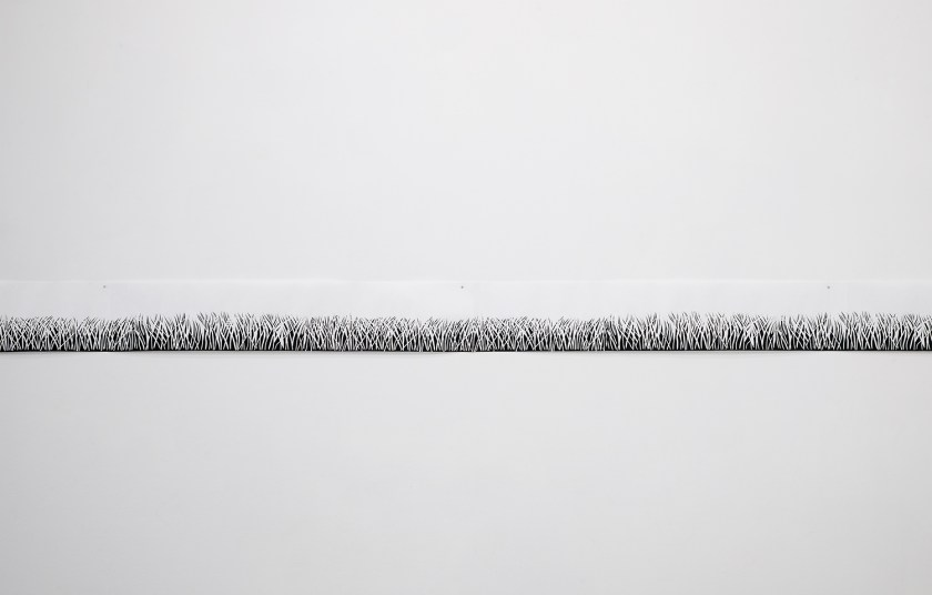 Untitled (Midwest Panorama) by Alejandro Waskavich. A long black and white print depicts a long stretch of a field against a white wall. Image courtesy of Greg Ruffing.