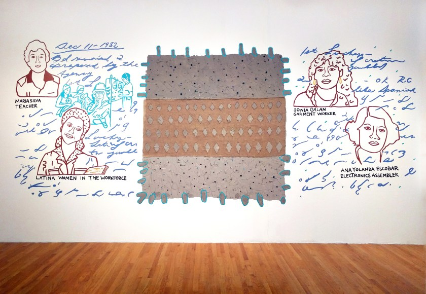 """Where is you spirit now?,"" 2017. Installation responding to the United Farm Workers archives from Wayne State University in Glass Curtain Gallery at Columbia College Chicago. Graphic portraits of women workers are painted in a minimal line drawing style onto the wall. The images are surrounded by handwriting and marks painted in blue and surround a brown and gray rectangular textile alternating geometric patterns and colors in three parts."