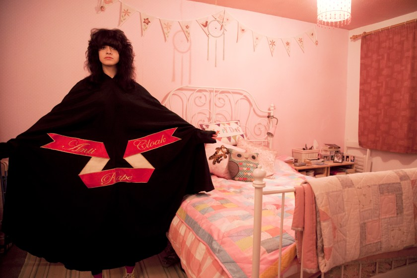 "Sarah Maple, Bedroom Cloak, 2015. C-type matt photograph, 15.75 x 23.5 inches. Maple spreads her arms wide to show the text of her ""Anti-Rape Cloak"" as she stands in a pink bedroom. Photo courtesy of the Ukrainian Institute of Modern Art."