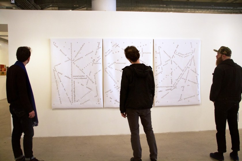 The photograph shows an interior white wall of a gallery space, on which three large pieces of canvas hang unframed and immediately adjacent to each other. Three people stand with their backs to the camera, looking at the canvases. On and across the canvases are words and phrases (written in black) that are oriented in various directions, curve, intersect, and more.