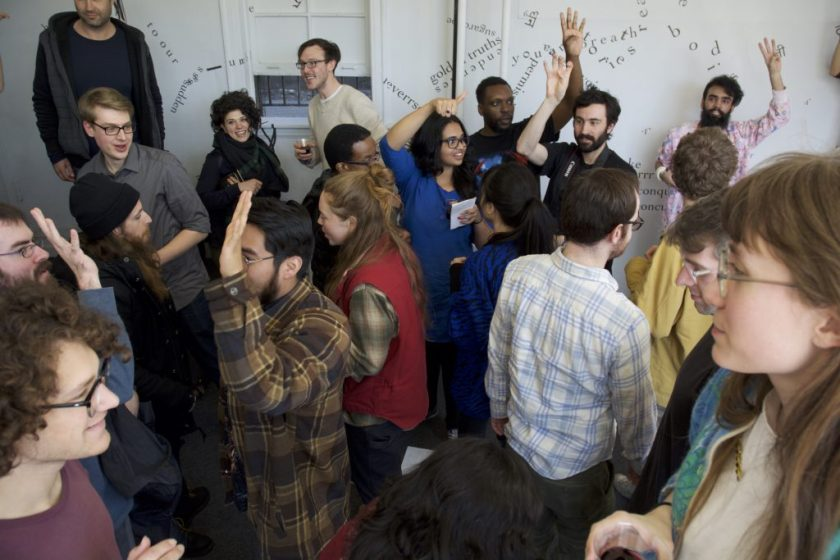 Approximately 20 people circulate inside the gallery, some close to the camera and some farther away. They appear to be moving in different directions than each other and several are raising their hands in the air. Many are smiling or laughing.