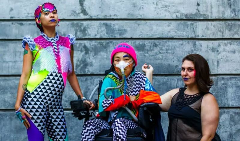 This image shows three people posing in front of a concrete wall. The person on the left is standing, at center, seated in a motorized wheelchair and wearing a breathing apparatus, and at right, kneeling. All are wearing brightly colored clothing with bold patterns.