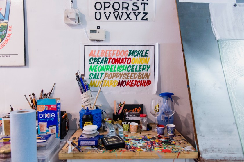 Image: Close up of various materials and tools used by Kelsey and Andrew. There are signs on the wall and colorful paint on the table. Photo by Ryan Edmund Thiel.