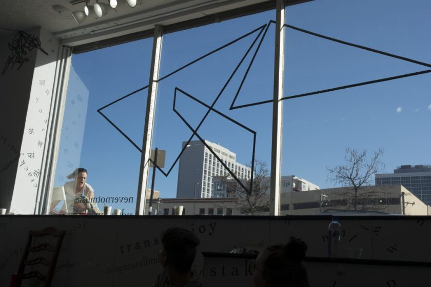This photo shows the gallery's large front window (with a motif of intersecting triangular shapes made of black vinyl) from the inside, and the blue sky beyond. Outside, the performer is visible through the bottom-left corner of the window. She holds something in her left arm as she moves toward the window, seemingly screaming. Inside, around the edges of the photograph, black vinyl letters are installed directly onto the white gallery walls, in the form of words and phrases in English and Hindi. Text appears in different sizes and spatial orientations (e.g., right-side up, upside-down, diagonal, vertical, and organic shapes), with some words/phrases expanded in space, condensed, or intersecting with other text. Gestural drawings—also made of black vinyl—are shown on the top left-hand side of the image. Low and very shadowy in the foreground are two audience members, sitting on the gallery floor with heads twisted toward the performer outside.