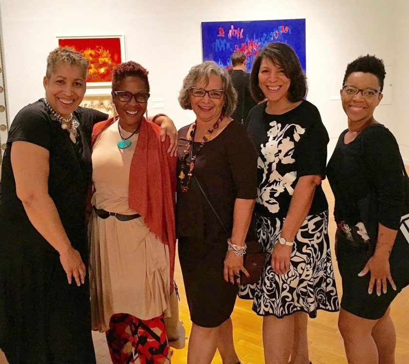 From left to right, Candace Hunter, Leslie Guy, Madeline Murphy Rabb, Michelle Bibbs, and myself at the opening reception of Norman Lewis' exhibition at the Chicago Cultural Center in September 2016. The image shows five women from the knee up, standing side by side with two small paintings on the wall in the background. Photo courtesy of Candace Hunter.
