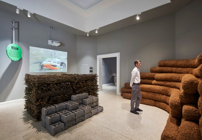 Ecological Citizens by SCAPE at the 2018 U.S. Pavilion. The image shows an installation view of an exhibition space. On the wall to the left there is a projected image. On the wall to the right there are stacks of long, brown tubes. In the center of the room is a neatly stacked cluster of wood sticks and cinderblocks. There is a person standing in the middle of the gallery space, studying the works. Photo © Tom Harris. Courtesy of the School of the Art Institute of Chicago and the University of Chicago.