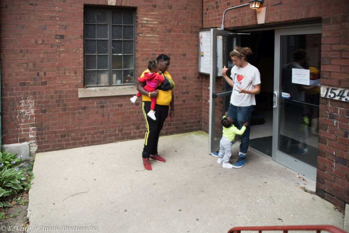 IMAGE: AnnMarie Brown stands outside the doors of United Church of Rogers Park with Circles & Ciphers Director of Operations, Evan Okun. AnnMarie is holding one child on her right hip while another is grasping Evan's pants legs.