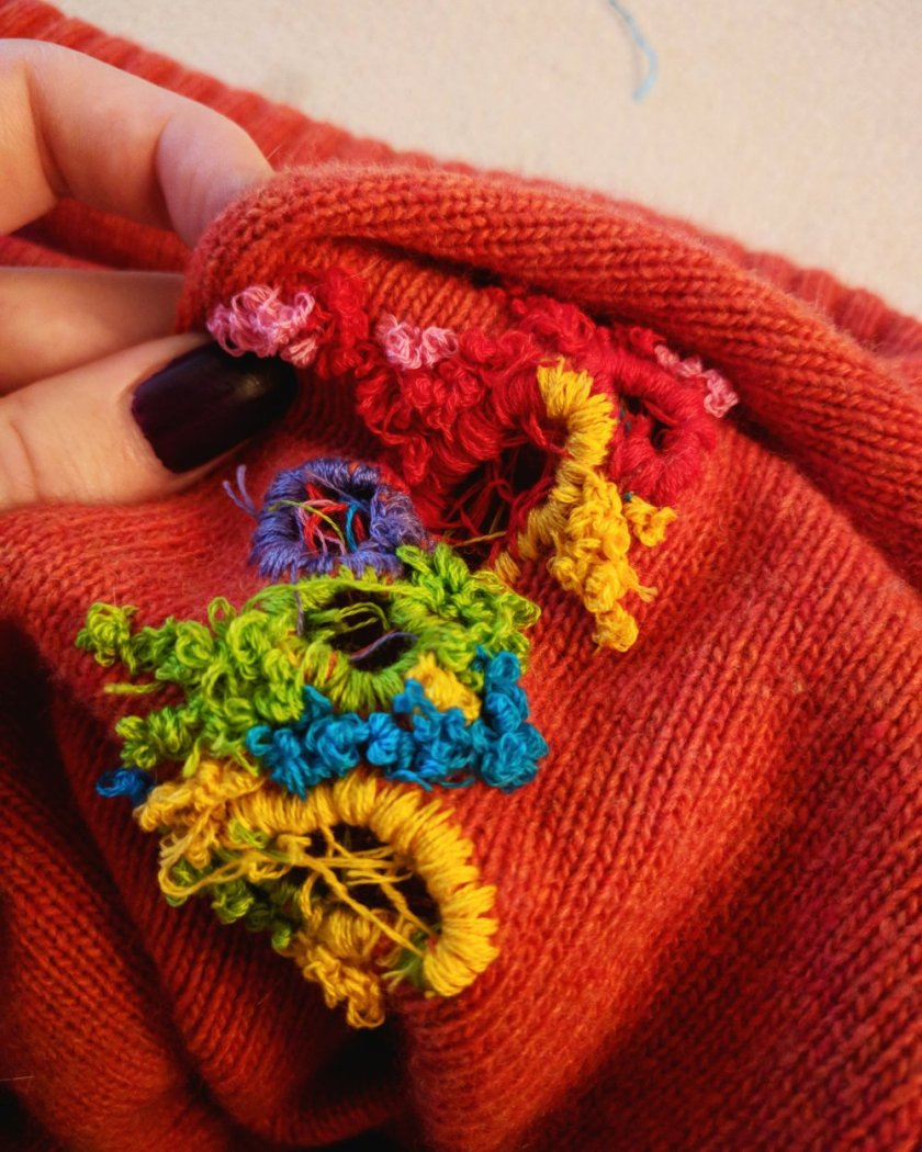 Image: Leslie Rose's hand holds up a detail of one of her embroidered garments. Salmon colored knit fabric is stitched with yellow, blue, green, purple, red, and light pink thread. Holes have been embroidered around and webbed over. Image courtesy of the artist.