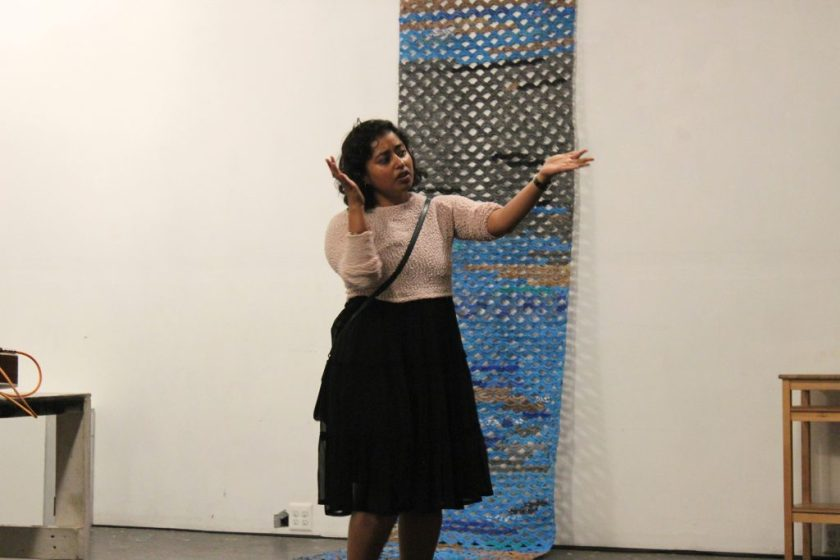 """Image: Udita Upadhyaya at the """"nevernotmusic"""" book release at TriTriangle. The artist stands at the center of the image, gesturing with both arms while speaking. Hanging on the wall behind Udita and extending onto the floor is a blue, grey, brown, and black artwork by Jerry Bleem, which was crocheted as part of a performance in response to Udita's score, """"Dear Jerry and Nick: Hold (a hand a spine a heart a whole self)."""" Udita wears a light-colored, textured sweater and black skirt. Photo by Caleb Neubauer."""