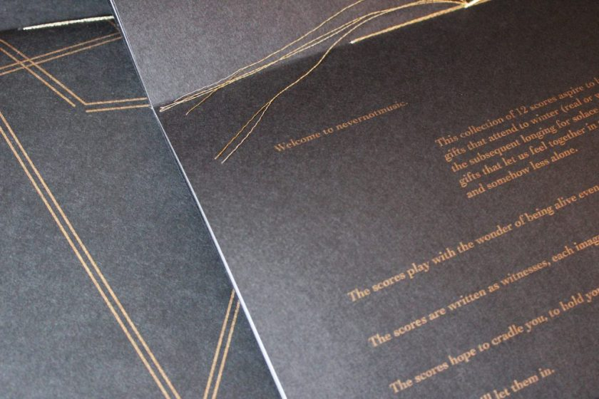 """Image: Udita Upadhyaya's book """"nevernotmusic"""" (detail). The book lies open to the centerfold, showing black paper, gold thread, and gold type. Part of the lower page is visible, with the text beginning, """"Welcome to nevernotmusic,"""" and including part of a description of the project of 12 scores and phrases like """"The scores play with the wonder of being alive even…"""" and """"The scores are written as witnesses…."""" Behind the open centerfold is part of the front cover of another copy. Photo by Caleb Neubauer."""