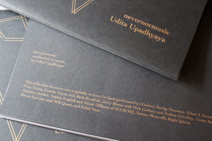 """Image: Udita Upadhyaya's book """"nevernotmusic"""" (detail). Three copies are in a loose pile, showing parts of the front cover and of the back cover (beginning with """"nevernotmusic / a collection of scores / by Udita Upadhyaya"""" and listing the performers for whom the scores were originally written). Text and motifs are in gold on black paper. Photo by Caleb Neubauer."""