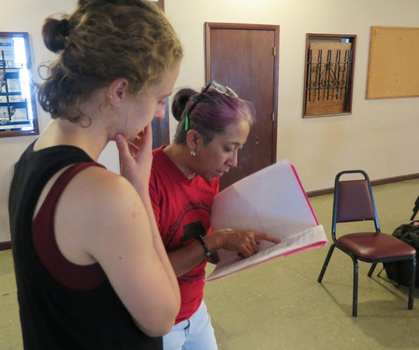 Image: Maxine Patronik (left) and Lani T. Montreal (right) at a rehearsal for their Body Passages piece at the Chicago Danztheatre Ensemble Auditorium. The artists stand next to each other, right sides in profile, looking down at a piece of paper in a folder in Lani's hand. Lani points toward the center of the page as Maxine looks on, right hand to her face. Lani wears a red t-shirt and light jeans. Maxine wears a black tank-top with a maroon top underneath. Covered windows, a door, a bulletin board, and chairs are in the background. Photo by Marya Spont-Lemus.