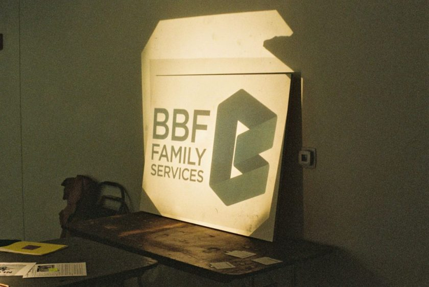 Image: The BBF Family Services logo is shown from a projector onto a large board leaned on top of a table against a dark wall. Photo by Eric K. Roberts.
