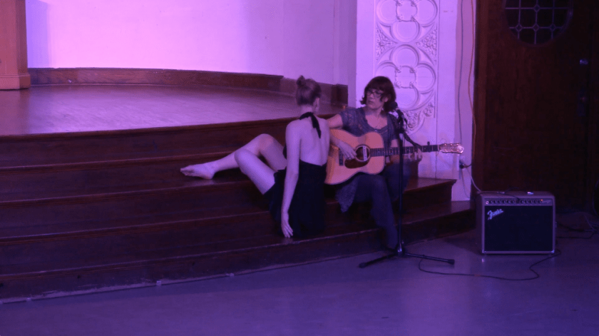 "Image: Carly Broutman and Michelle Shafer performing in ""Wax."" This slightly closer shot shows Carly and Michelle sitting on the stage steps, turning to look at each other. Carly's back is to the audience and, though her back is positioned straight-up, her legs are folded or extended onto higher stairs than where she is sitting. Michelle holds an acoustic guitar and sits more commonly, with one foot on a lower step and another on the floor. The lighting is dim and pink-purple. Still from a video by John Borowski."